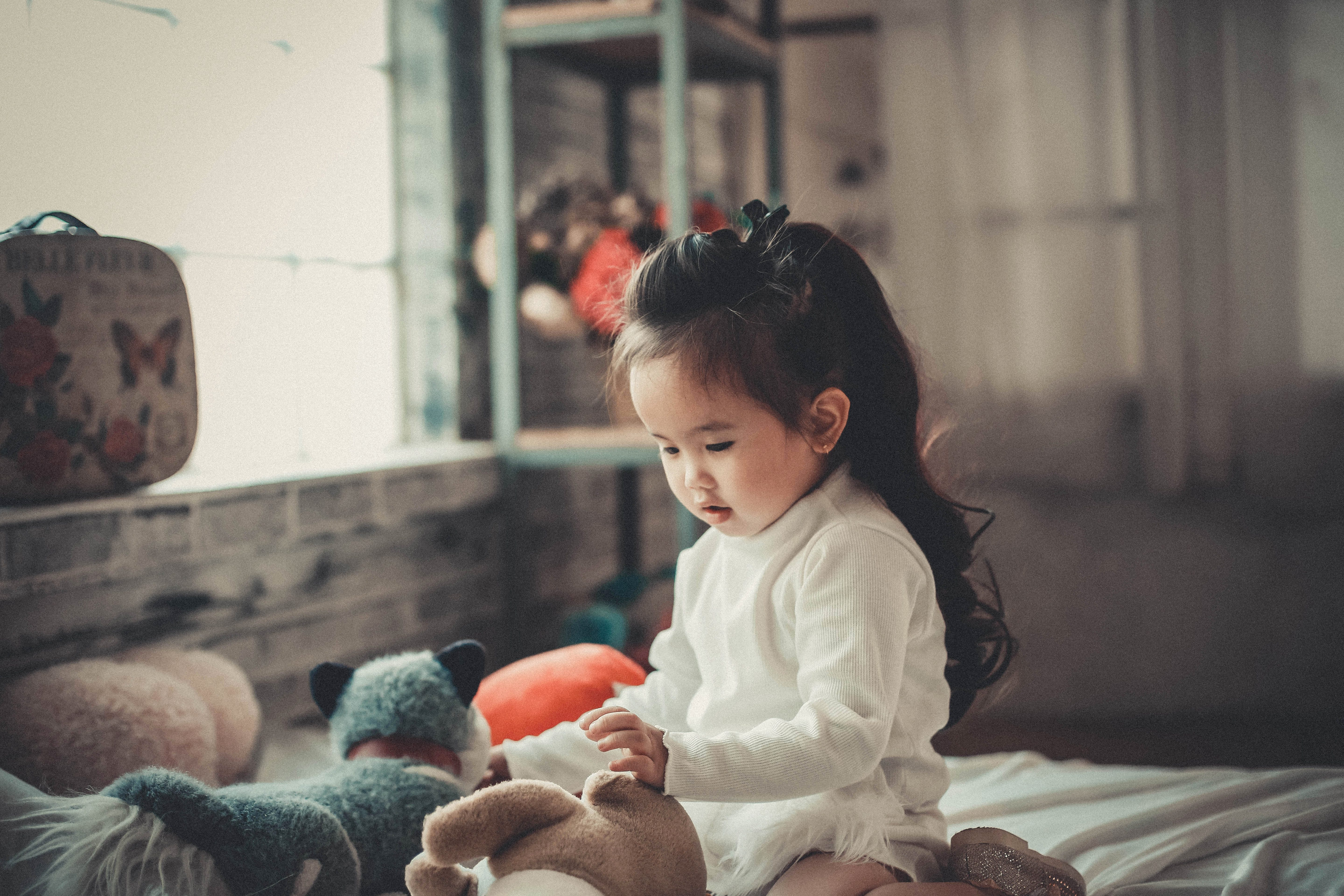 small girl with soft toys